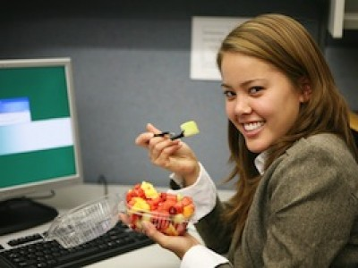a pretty woman taking a break from the computer and eating fruit