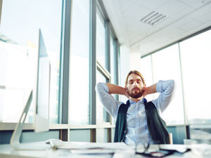 Man-stretching-and-relaxing-at-his-desk